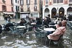 Turisté a místní obyvatelé sedí ve venkovní části restaurace na zaplavené ulici v italských Benátkách