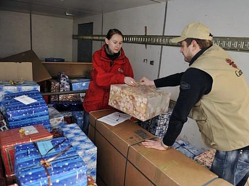 Pracovníci olomoucké Arcidiecézní charity Veronika Mechová (vlevo) a Rostislav Strojvuz nakládají 23. prosince do kamionu připravené vánoční dárky pro dětské domovy a sociální centra na Ukrajině