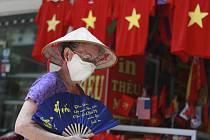 Žena s rouškou na ulici viernamské Hanoje