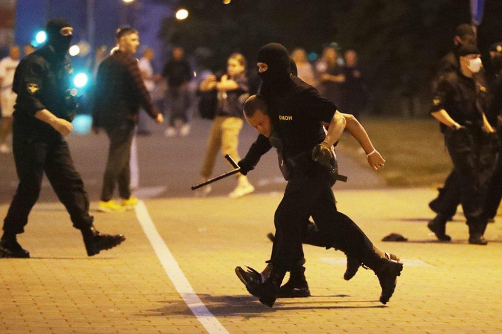 Policie zatýká demonstranta během protivládních protestů v ulicích Minsku.