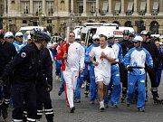 Britští policisté zatýkají demonstranta, který chtěl minimaxem uhasit olympijskou pochodeň.