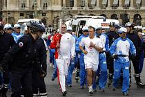 Čínští strážci olympijského ohně (v modrém) doprovázejí běžce s pochodní.