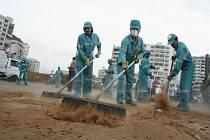 Dělníci uklízejí ulici v Bejrútu poté, co z ní buldozery odstranily navezené hromady písku, tvořící barikády.