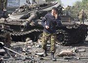Telefonující ruský voják u zničeného tanku