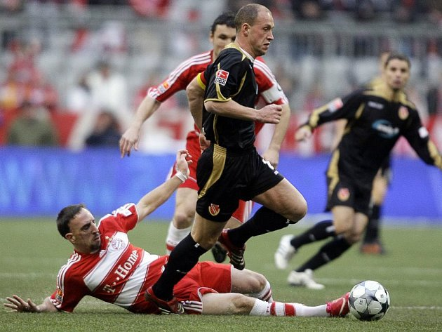 Francouz Franck Ribery  z Bayernu atakuje Timo Rosta z týmu Energie Cottbus.