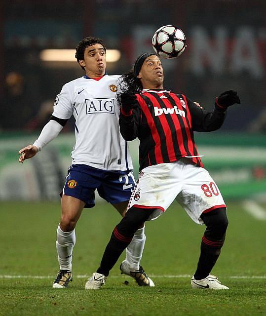 Ronaldinho z AC Milán (vpravo) kontroluje míč před dotírajícím Rafaelem da Silvou v osmifinále Ligy mistrů.