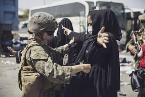 Američtí vojáci kontrolují na letišti v Kábulu civilisty, kteří usilují o evakuaci v jednom z letadel mířících na západ
