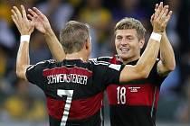 Fotbalisté Německa Bastian Schweinsteiger (vlevo) a Toni Kroos se radují z gólu proti Brazílii.