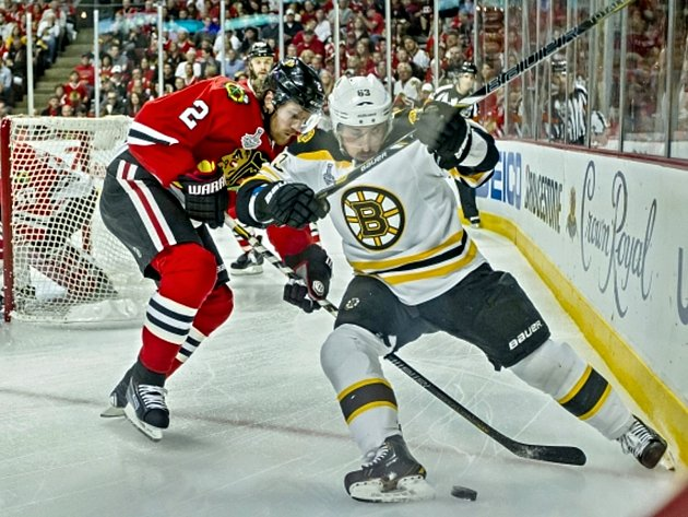 Duncan Keith (Chicago Blackhawks) a Brad Marchand (Boston Bruins) v souboji o puk ve druhém utkání finále play off NHL.