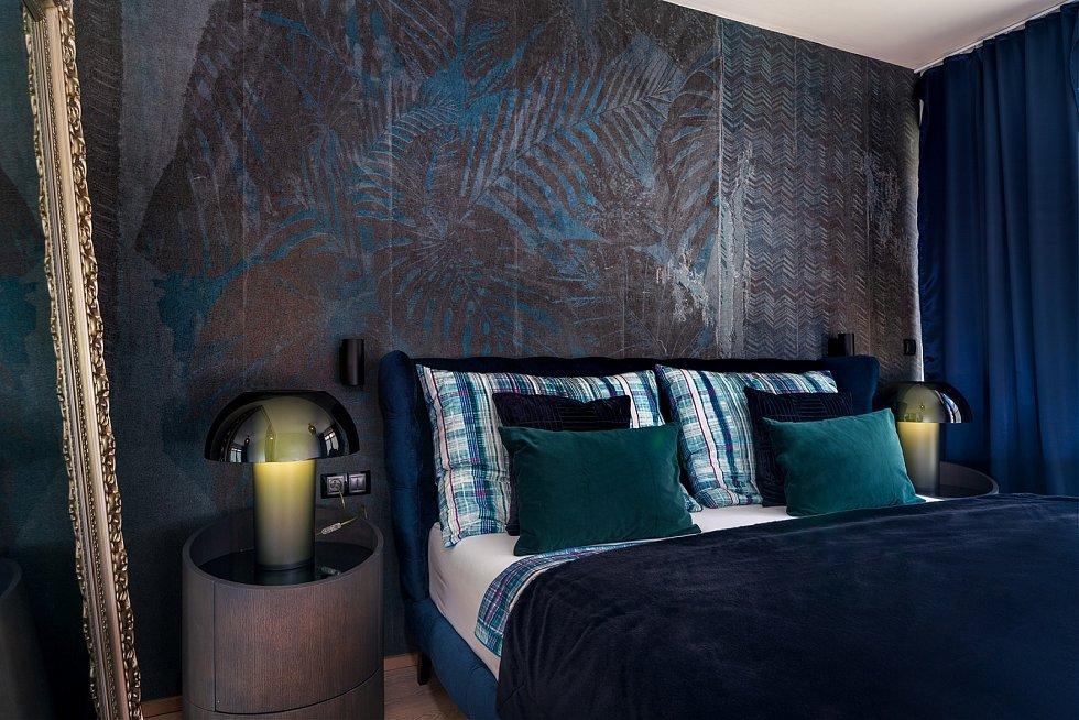 Propojení historizujících prvků s moderními napomáhá i tapeta s potemnělým motivem tropických rostlin na pozadí stárnoucí zdi, kterou umístila na stěnu v ložnici.