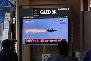 Lidé na železniční stanici v Soulu sledují na televizní obrazovce střelu vypálenou armádou KLDR