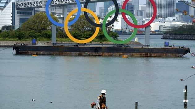 Pracovník seká trávu poblíž obřích olympijských kruhů v tokijské čtvrti Odaiba