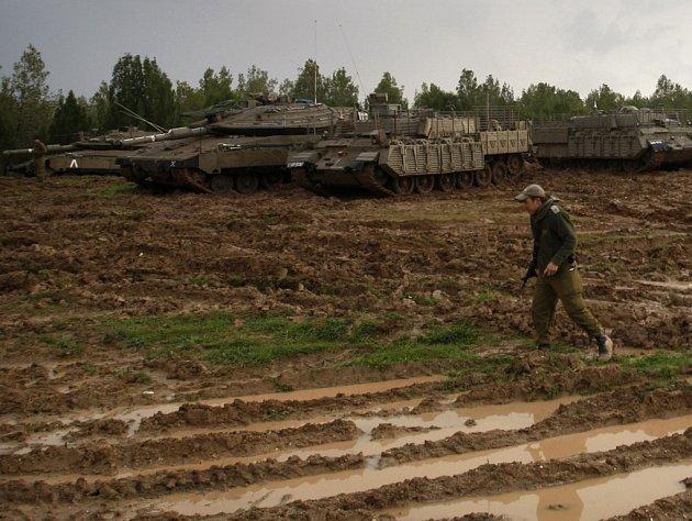 Voják pochoduje podél jedoucích tanků v pásmu Gazy.