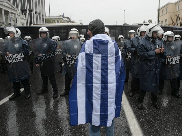 Demonstrant zahalený do řecké vlajky se postavil proti kordonu policistů v Aténách.