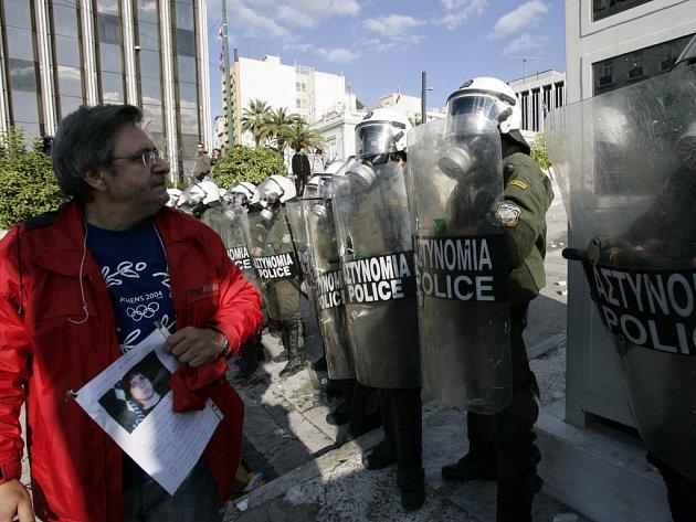 Muž třímá fotografii zastřeleného patnáctiletého Alexandrose Grigoropouluse před kordónem policistů v Aténách.