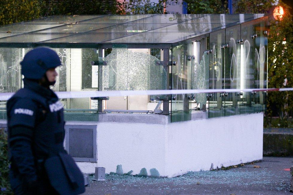 Rakouský policista hlídkuje 3. listopadu 2020 ve Vídni den po střeleckém útoku, v pozadí vjezd do garáží s rozbitými skly.