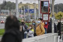 Lidé v rouškách na stanici MHD v Praze