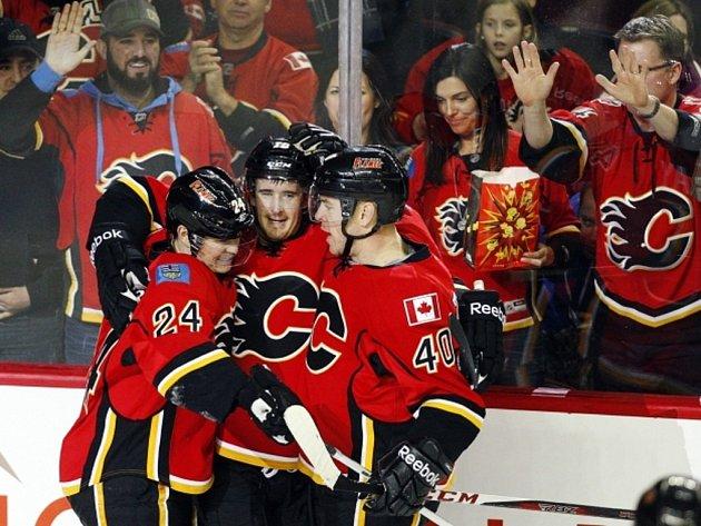 Hokejisté Calgary (zleva) Jiří Hudler, Roman Červenka a Alex Tanguay se radují z gólu proti Jágrovu Dallasu.