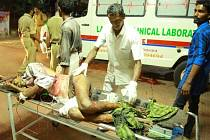Záchranáři ošetřují popáleného muže. V indickém chrámu zahynuly desítky lidí.