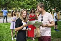 Učitel Jakub Siegl (vpravo) předává vysvědčení studentce na pikniku u školy, na kterém se 26. června 2020 se školním rokem poznamenaným koronavirovou pandemií rozloučila kvarta plzeňského Gymnázia Františka Křižíka