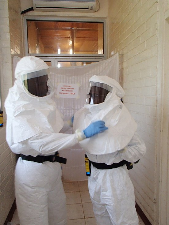 Liberijští laboranti Aaron Momolu (vlevo) a Lawrence Fakoli si před vstupem do uzavřeného prostoru pro testování vzorků nasadili ochrannou výstroj
