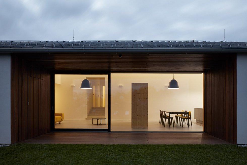Maximální vzdušnost dodávají i velká bezrámová okna, která spojují přes krytou venkovní lodžii interiér se zahradou.