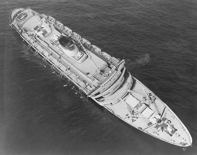 Nakloněný parník Andrea Doria jen pár hodin před tím, než se definitivně ponořil na mořské dno.