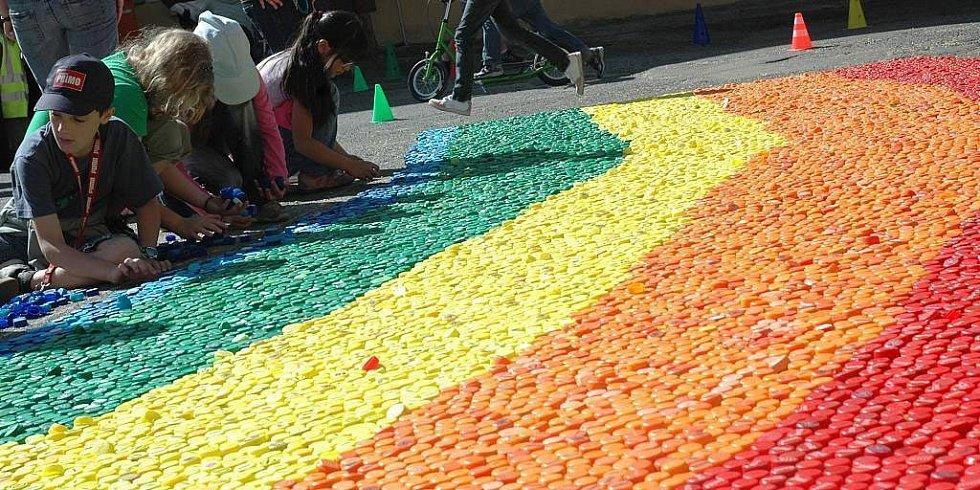 Barevná duha z plastových víček od PET lahví zdobila po celou středu Škroupovo náměstí v České Lípě. Místní školáci na ní v rámci oslav Dne Země pracovali celé dopoledne.