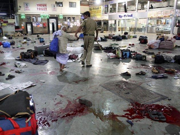Policista odvádí starou ženu z nádraží v indické Bombaji, kde předtím zaútočil terorista. Extrémisté zaútočili 26. listopadu na deseti místech ve městě, včetně dvou hotelů a zabili nejméně 171 lidí.