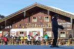Lyžař projíždějící kolem zaplněné restaurační zahrádky. Takový pohled v lyžařském středisku položeném ve vyšší nadmořské výšce, než má vrchol nejvyšší české hory, najdete na každém kroku.