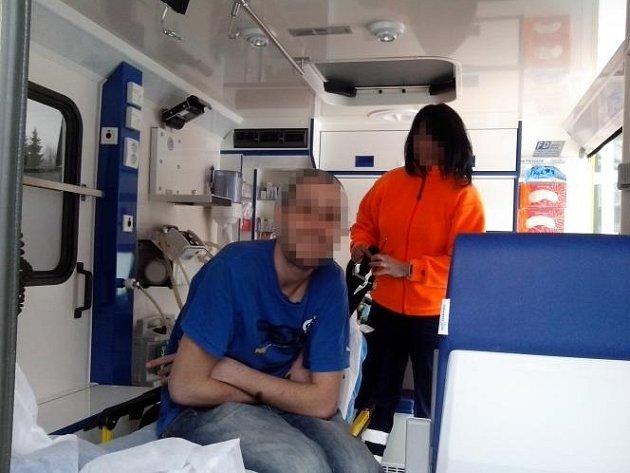 Spokojený pacient se sestrou před zajištěním na přepravním lehátku v sanitce.