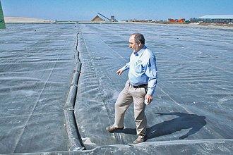 Inženýr Douglas Williams kráčí po plachtě zakrývající obrovskou nádrž s kravskou mrvou.