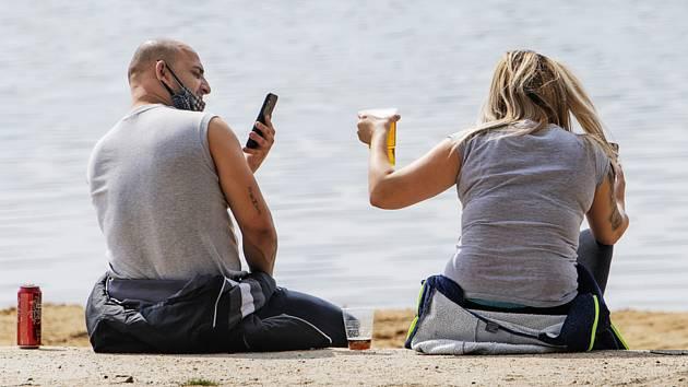 Lidé 4. dubna 2020 tráví slunné jarní odpoledne u Boleveckého rybníka v Plzni. Kvůli pandemii koronaviru platí vládní nařízení, které omezuje soustředění velkého množství lidí na jednom místě