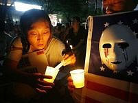 Korejka zapaluje v soulu svíci na demonstraci proti válce a za osvobození korejských rukojmích.