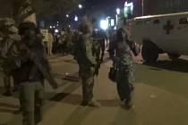 Osvobozená žena prochází kolem francouzských speciálních jednotek poblíž napadeného hotelu Splendid.
