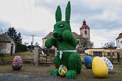Velikonoční dekorace v podobě velkého zajíce a vajíček v Rynolticích na Liberecku, v pozadí je kostel svaté Barbory. Snímek je z 2. dubna.