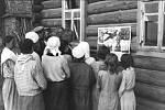 Civilisté si prohlížejí agitační německý plakát velebící Wehrmacht