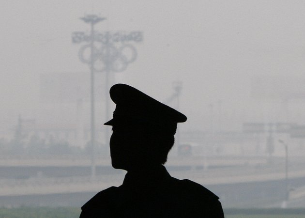 Čínský policista hlídkuje u pekingského letiště, pro smog ale daleko nedohlédne.