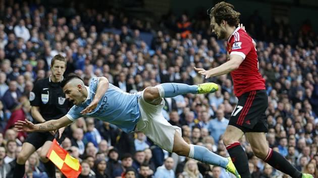 Sergio Agüero z Manchesteru City (vlevo) se poroučí k zemi před Daleyem Blindem z Manchesteru United.