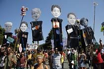 Protestující aktivisté nesou fotky představitelů G7
