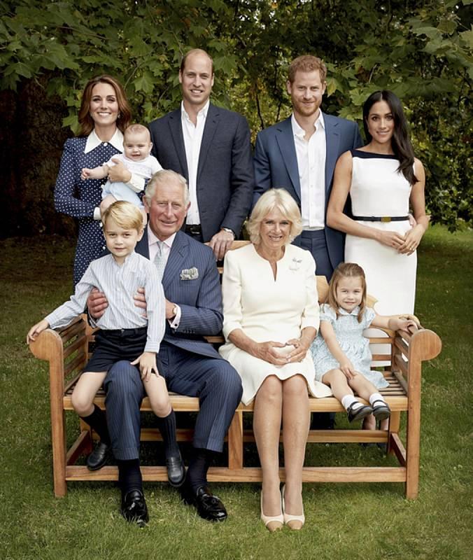 Britský princ Charles (v popředí) se svou manželkou Camillou a vnoučaty princem Georgem a princeznou Charlotte. V horní řadě stojí za ním jeho syn William s manželkou Kate a vnoučetem Louisem a na pravé straně syn Harry s manželkou Meghan.