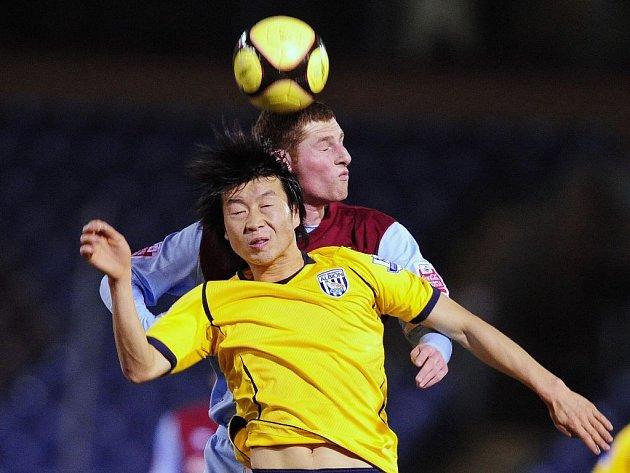Záložník Burnley Chris McCann (vpravo) v souboji s Kim Do-heon.