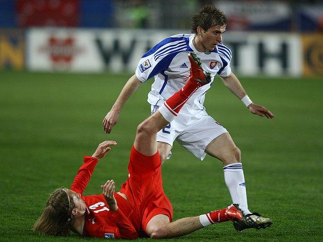 Jaroslav Plašil (v červeném) se ocitl na zemi v souboji s Peterem Pekaríkem.
