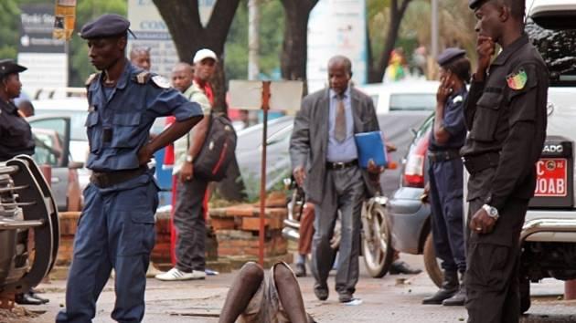 Guinejští policisté hlídkují u těla muže, který zkolaboval na následky eboly na ulici.