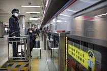 Lidé s maskami na obličejích v pekingském metru.