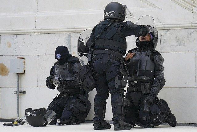 Vyčerpaní těžkooděnci, kteří zasahovali proti demonstrantům u Kapitolu.