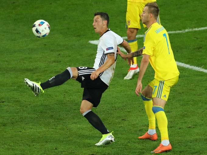 Mesut Özil z Německa (vlevo) si zpracovává míč před Andrijem Jarmolenkem z Ukrajiny.