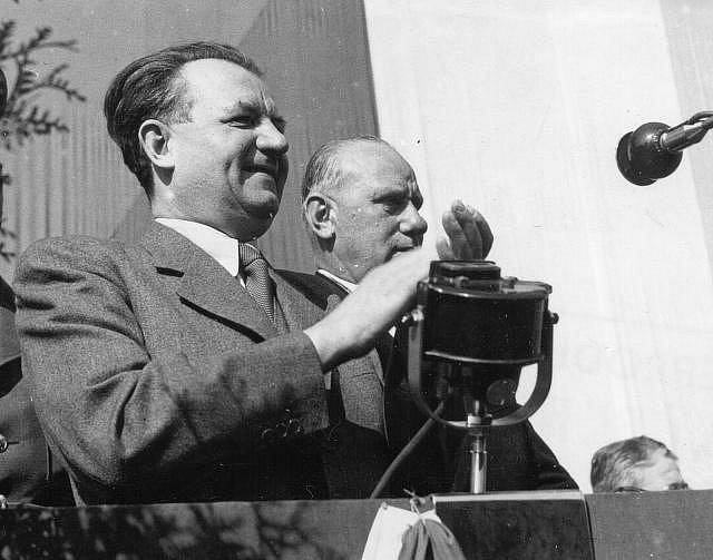 Klement Gottwald na řečnické tribuně, vpravo za ním Václav Nosek