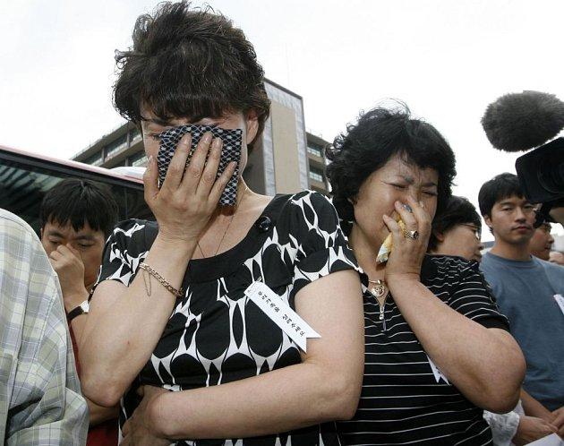 OČI PRO PLÁČ. Zoufalí příbuzní mladých korejských misionářů unesených před dvěma týdny v Afghánistánu talibanskými povstalci si utírají slzy z očí během tiskové konference před americkou ambasádou v Soulu, kam p řišli požádat Američany o pomoc.