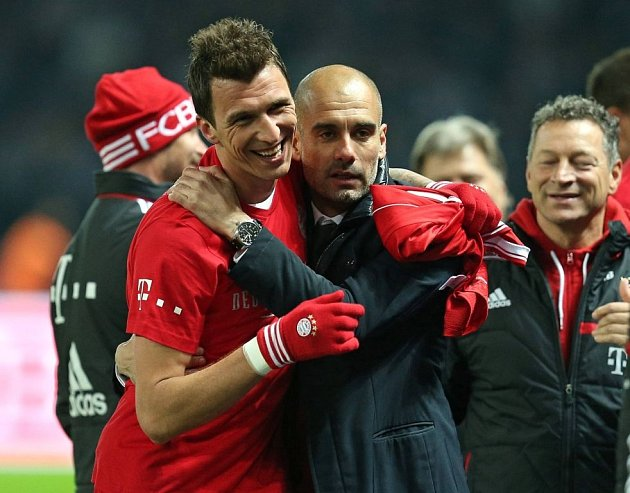 Útočník Mario Mandžukič (vlevo) a trenér Pep Guardiola se radují: fotbalisté Bayernu Mnichov získali rekordní 24. bundesligový titul.